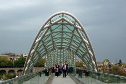 People walking through Tbilisi Bridge of Peace
